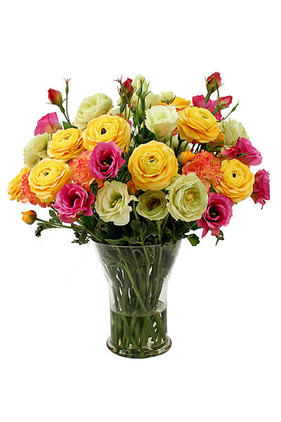 Mix of happy spring flowers, yellow and orange ranankulus in with bright purple and cream lisianthus